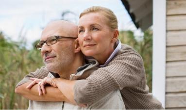 Eine Frau umarmt ihren Mann vor einem Holzhaus, während sie in die Ferne sehen