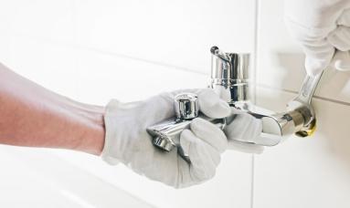 Bild, wie ein Monteur eine Badarmatur anbringt