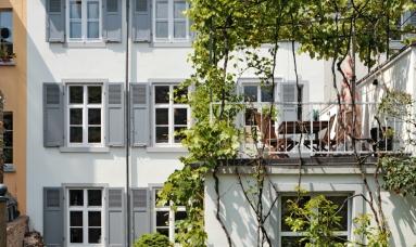 dreistöckiges Haus mit grauen Fensterläden und Dachterasse