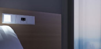 Das LED-Leselicht von Jung als Schalter mit Steckdose an Bett montiert.