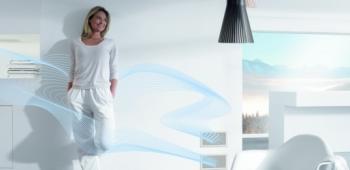 Eine Frau geniesst stehend die mollige Wärme aus der Zehnder Wandlüftung