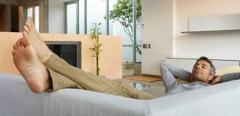 Ein entspannter Mann auf Couch im Wohnzimmer von Sto