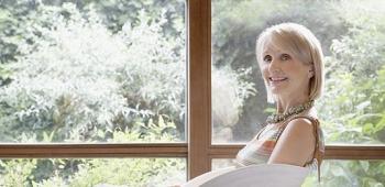 eine Frau sitzt lächelnd in einem weißen Stuhl vor einem großen Fenster