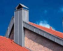 Abgestuftes Dach mit Blecheinfassung und zwei Schornsteinen
