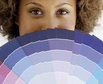 Eine Frau hält eine Farbpalette vor ihr Gesicht